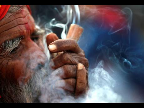 A Hindu holy man smokes marijuana in the courtyard of Pashupatinath temple during the Shivratri festival in Kathmandu, Nepal.