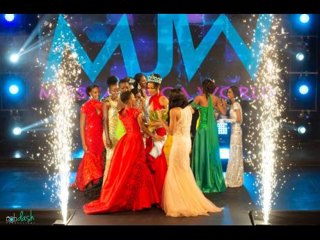 Newly-crowned queen Khalia Hall is surrounded by contestants in the 2021 Miss Jamaica World pageant.