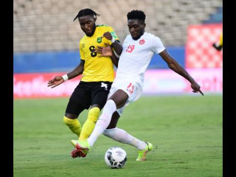 Jamaican defender Oneil Fisher (left) challenges Canada's Alphonso Davies during a FIFA World Cup qualifier between the two teams at the National Stadium on Sunday, October 10, 2021. The match ended 0-0.