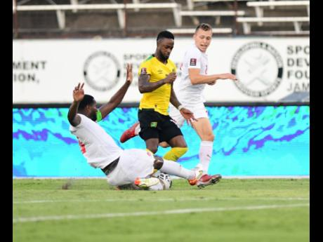 Jamaica's Junior Flemmings (centre) is tackled by Doneil Henry (left) and Alistair Johnston of Canada during Sunday's FIFA World Cup qualifying match at the National Stadium. The match ended 0-0.