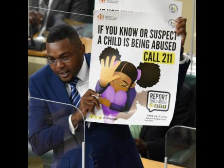 Robert Nesta Morgan, state minister in the Ministry of Education, shows a child-abuse poster in Parliament on Tuesday. The Clarendon North Central MP was making his debut contribution to the State of the Constituency Debate.