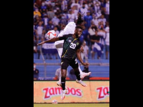 Jamaica's Kemar Lawrence (front) and Honduras' Alberth Elis jump for a header during a FIFA World Cup qualifying match  at the Metropolitan Olympic Stadium in San Pedro Sula, Honduras on Wednesday.
