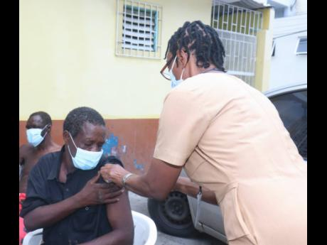 Nurse Jennifer Pearson administers the Johnson & Johnson vaccine to Leighton McFarlane on World Mental Health Day at the St James Parish Council Care Centre in Montego Bay.