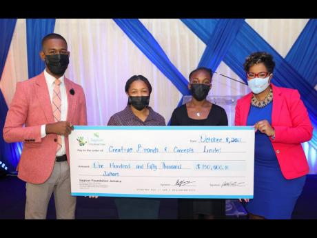 Fabian Gordon (left), financial adviser with the Sagicor Life Spanish Town branch, presents a symbolic cheque of $150,000 to Erica McKenzie (right), CEO, Creative Brands & Concepts Limited, to support the organisation's Live2Lead Youth Scholarship Award
