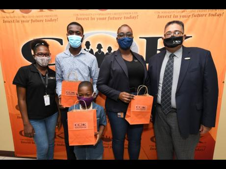 Deryke Smith (right), acting CEO of COK Sodality Co-operative Credit Union, poses with COK Scholarship awardees Ricardo Ricketts (second left); Abigale Scott (second right) and Trey-Sean Blackwood (front), whose mother, Rusheda Hall, is at left. This year