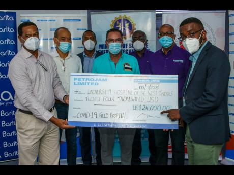 Minister of Science, Energy and Technology Daryl Vaz (centre) shares in Petrojam Limited's presentation of a cheque valued at US$24,000 to the University Hospital of the West Indies (UHWI) for the COVID field hospital initiative. Participating in the pre
