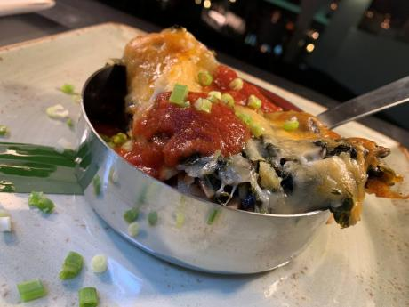 Callaloo, mushroom and ricotta broken lasagna, with fire toasted tomato coulis, fresh herbs, and Parmesan and mozzarella cheese.