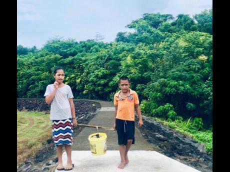 Young children cross the walkway to go to the local market to sell food in Samoa, a small island developing state in the Pacific. The walkway was created under the AF-funded project implemented by UNDP to protect against erosion and mudslides caused by sea