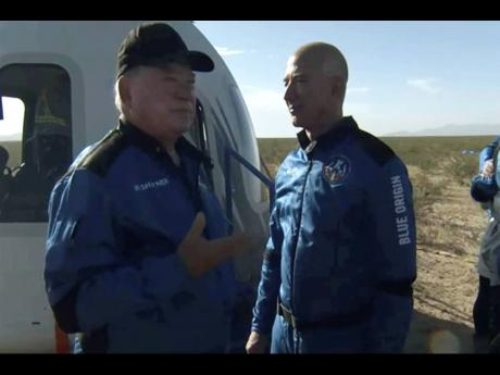 William Shatner (left), talks with Jeff Bezos about his experience after exiting the Blue Origin capsule near Van Horn, Texas, on Wednesday.