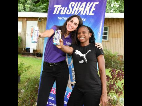 TruShake Marketing Manager Lauren Mahfood (left) poses with Olympian Megan Tapper, who signed a three-year deal to become the brand's ambassador, at a press conference in St Andrew yesterday.