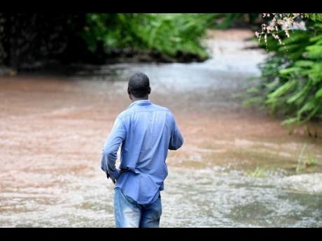 The driver of a Suzuki Grand Vitara SUV looks on at floodwaters after being rescued late last month. The vehicle was swept away after he tried to cross a flooded section of the gully in the vicinity of Charlton Avenue, St Andrew.