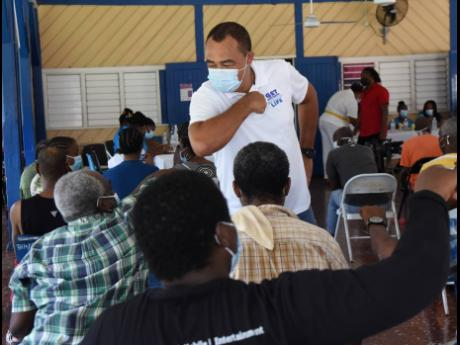 Health and Wellness Minister Dr Christopher Tufton (standing) greets patients at the Bellevue Hospital in Kingston during a vaccination drive at the mental health institution yesterday.