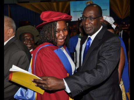 Dr Grace McLean gets a congratulatory hug from Ruel Reid as she graduated with her doctorate in philosophy on November 1, 2014. Reid resigned as education minister in 2019 and has been charged with corruption. The auditor general has called for a police in