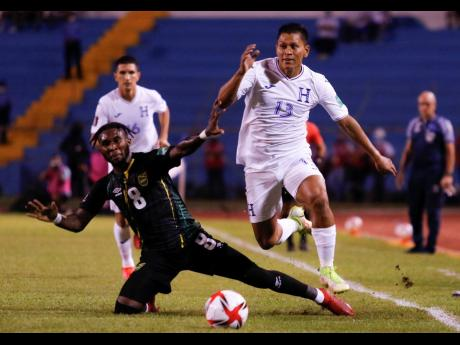 Jamaica's Oniel Fisher (left) and Honduras' Bryan Moya, compete for the ball during a FIFA World Cup qualifying match at Estadio Olímpico Metropolitano in San Pedro Sula, Honduras yesterday.