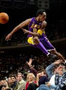 In this December 2001, file photo Los Angeles Lakers' Kobe Bryant jumps over a row of fans after saving the ball from going out of bounds in the second half of the Lakers 107-101 win over the Houston Rockets in Houston.