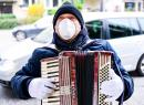 A musician plays in mask and gloves at the 'Isemarkt' street market in Hamburg, Germany, on Friday, March 20.