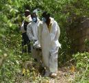 Personnel from the Sunset Funeral Home remove the body of a man from a shallow grave in Byles district near Kitson Town in St Catherine.