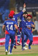 Afghanistan's Rashid Khan (second right) celebrates the wicket of Scotland's Brad Wheal (out of photo) during the Cricket Twenty20 World Cup match in Sharjah, United Arab Emirates, yesterday. Afghanistan won by 130 runs.